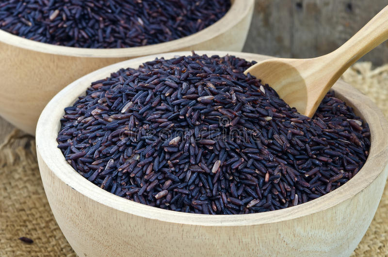 Purple Riceberry rice. Closeup of raw purple Riceberry rice in wooden blow, it is a crossbred between Thai Hom Nil (black jasmine rice) and white Jasmine rice stock images
