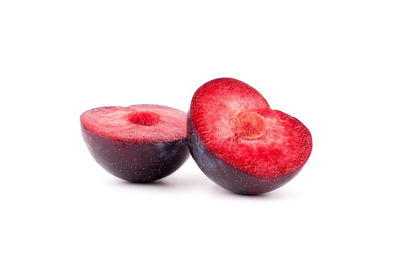 Purple ripe plum cut into two halves in shape of heart red inside on white background isolated close up macro royalty free stock photo