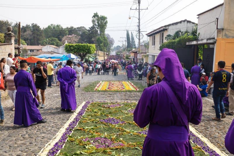 Purple robed mens die zich voor bloemtapijten bevinden de optocht van San Bartolome DE Becerra in 1a Avenida de bekijken stock afbeelding
