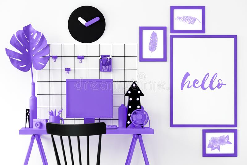 Purple room interior. With computer, black chair, posters, clock, plant, camera, cup with pens and decorations royalty free stock photo