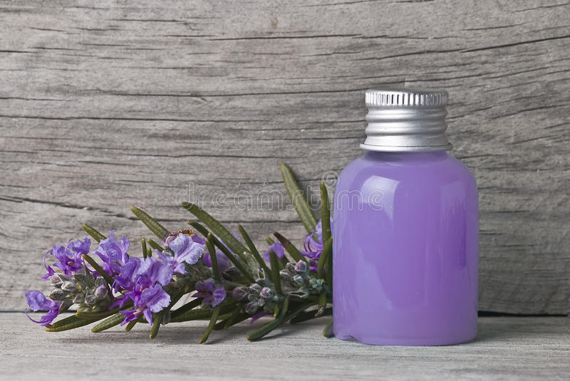 Purple shower gel. A jar with rosemary gel and a rosemary branch full of flowers stock images