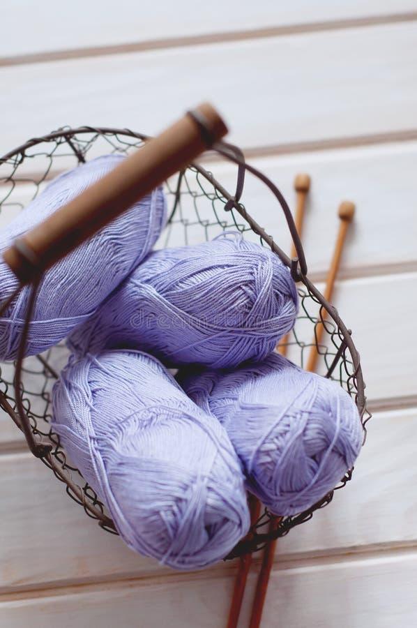 Purple skeins of cotton yarn in a basket. Light purple skeins of cotton yarn in a basket with wooden knitting needles stock photos