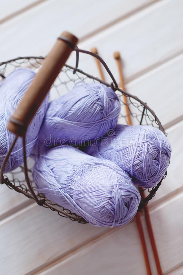 Purple skeins of cotton yarn in a basket. Light purple skeins of cotton yarn in a basket with wooden knitting needles royalty free stock photo