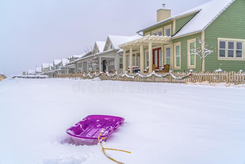 Purple sled against snow and homes in Daybreak stock photos