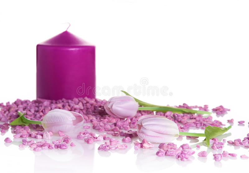 Purple spa treatment still life. Spa still life with purple andle, pink stones and lilac tulips royalty free stock image