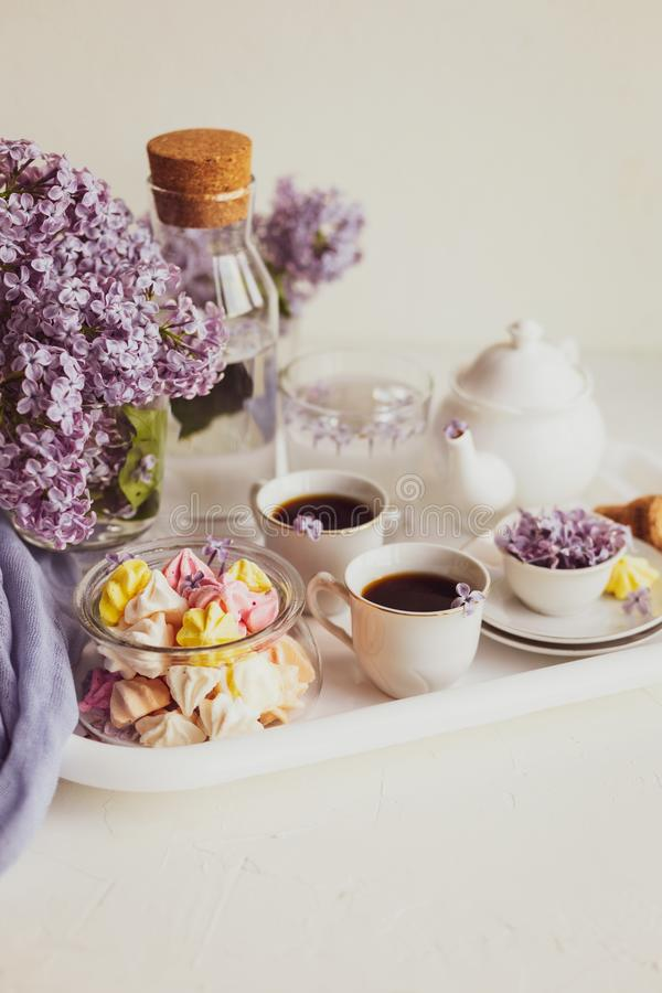 Purple spring lilac flowers  breakfast still life. Purple spring lilac flowers still life on white background in the morning. Tea-time or breakfast with black stock photo