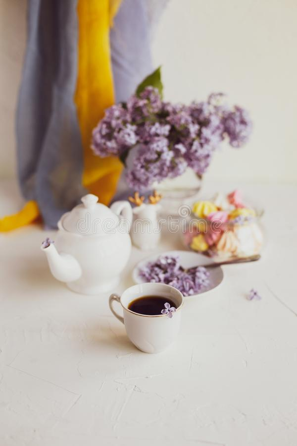Purple spring lilac flowers  breakfast still life. Purple spring lilac flowers still life on white background in the morning. Tea-time or breakfast with black stock photos