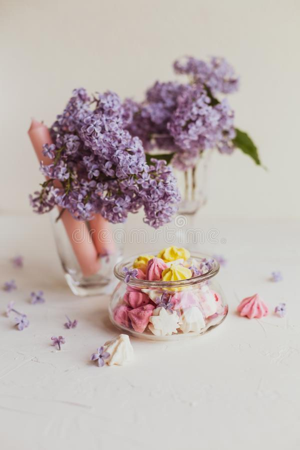 Purple spring lilac flowers still life on white. Purple spring lilac flowers still life  with candies on white background in the morning stock photos