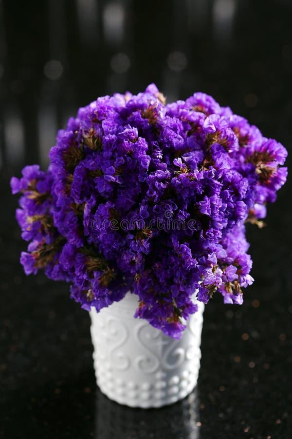 Purple Statice flowers in white jar stock image