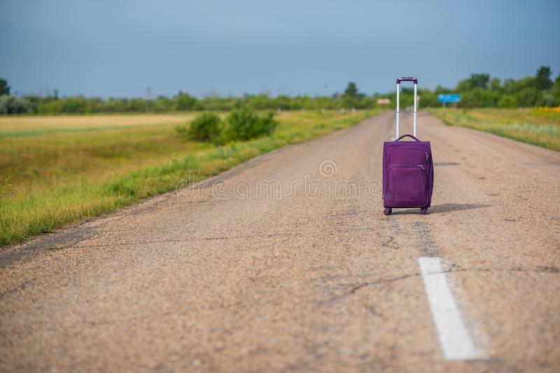Purple suitcase on wheels with a raised handle stands in the middle of an empty asphalt road in the fields. Summer, Sunny weather. Travel royalty free stock photography