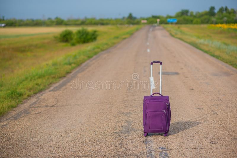 Purple suitcase on wheels with a raised handle stands in the middle of an empty asphalt road in the fields. Summer, Sunny weather. Travel royalty free stock images