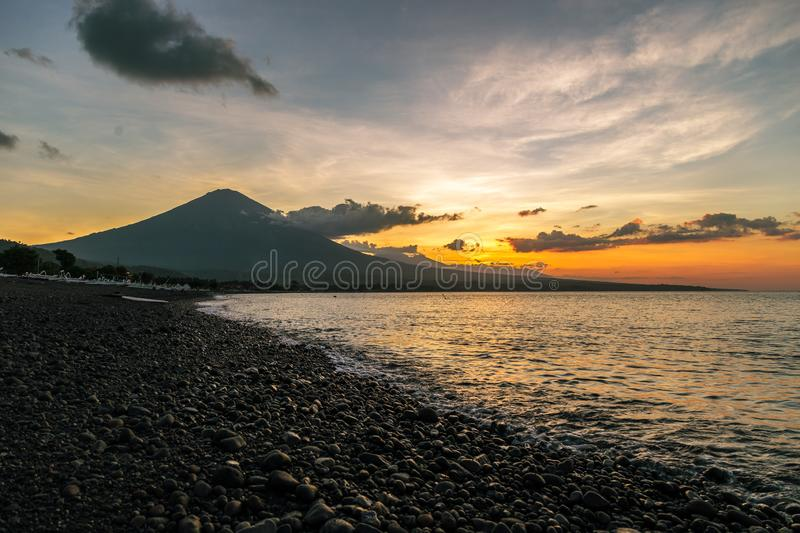 Purple sunset in Amed with the largest volcano on the Agung in Bali, Indonesia stock photos