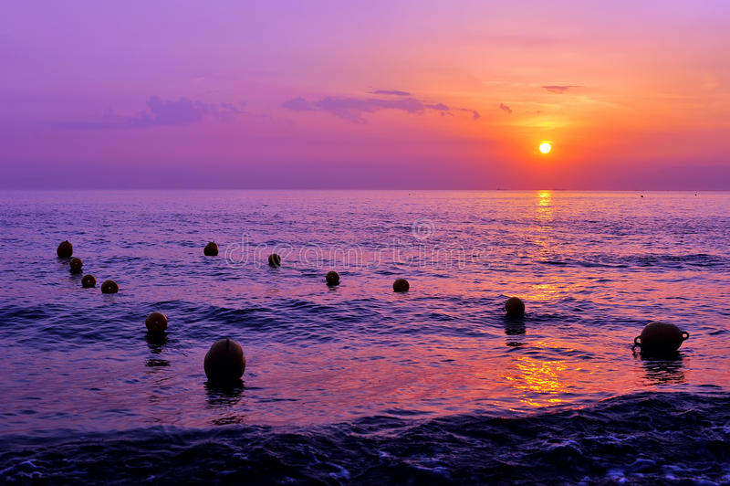 Purple sunset and lineas of buoys on the sea. Purple sunset shoreline with and lines of buoys on water royalty free stock photography