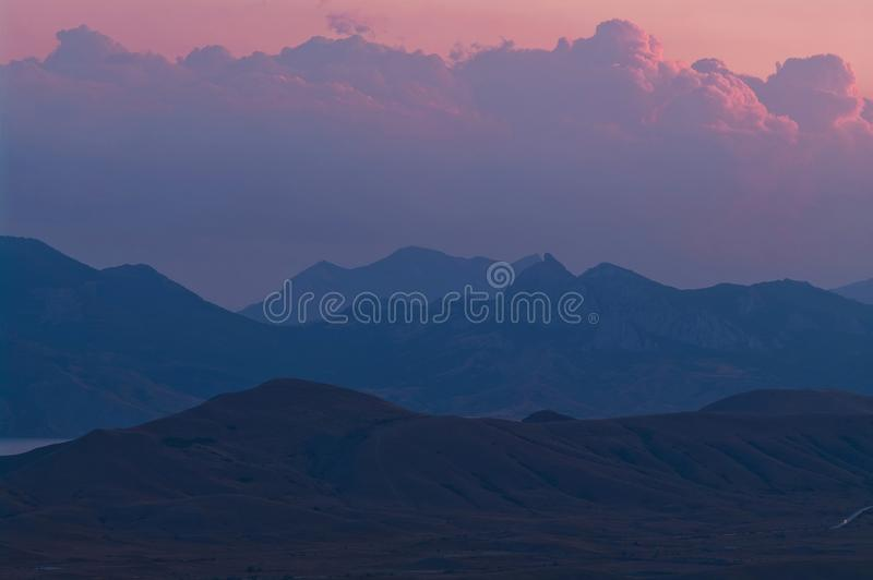 Purple sunset in the mountains. Evening landscape in a hilly area with purple clouds royalty free stock image