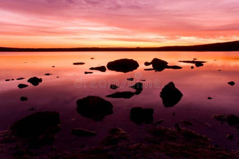 Purple sunset over ocean water stock image