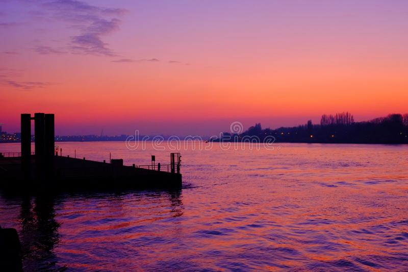 Purple sunset over the river. Purple sunset reflected in the water of the river Scheld in Antwerp, Belgium, Europe royalty free stock images