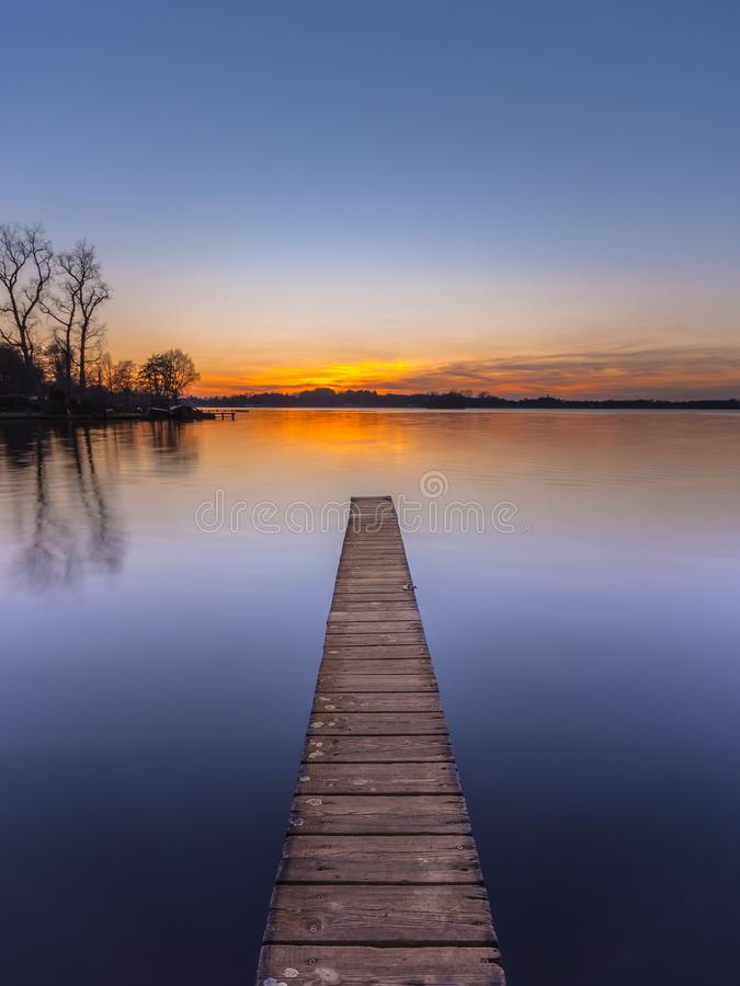 Purple Sunset over Serene Lake vertical. Purple Sunset over Serene Water of Lake Paterwoldsemeer, Netherlands stock photography