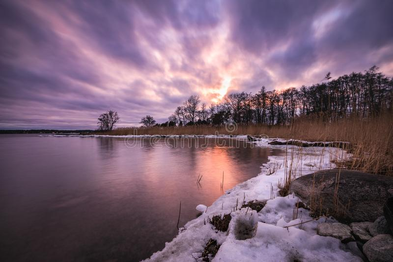 A purple sunset over a winter landscape by the sea. There is snow on the ground and the colorful sky is reflected in the smooth water royalty free stock photo