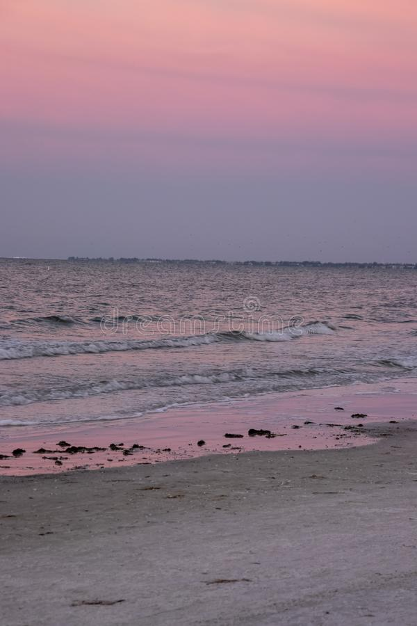 Purple sunset reflects onto water and sand of Fort Myers Beach, royalty free stock images