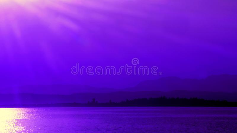 Purple sunset at Sirmione on lake garda in Italy. Mountains and castle of Sirmione on peninsula in Lago di Garda in Italy in evening royalty free stock photography