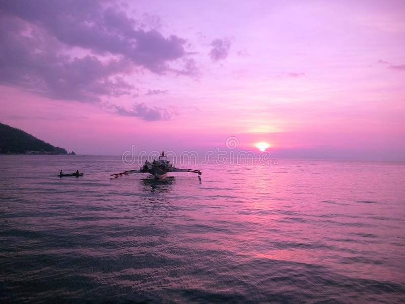 Purple sunset. Violet or purple sunset with ocean view and a cute boat on the way to Masasa Batabgas Philippines stock photography