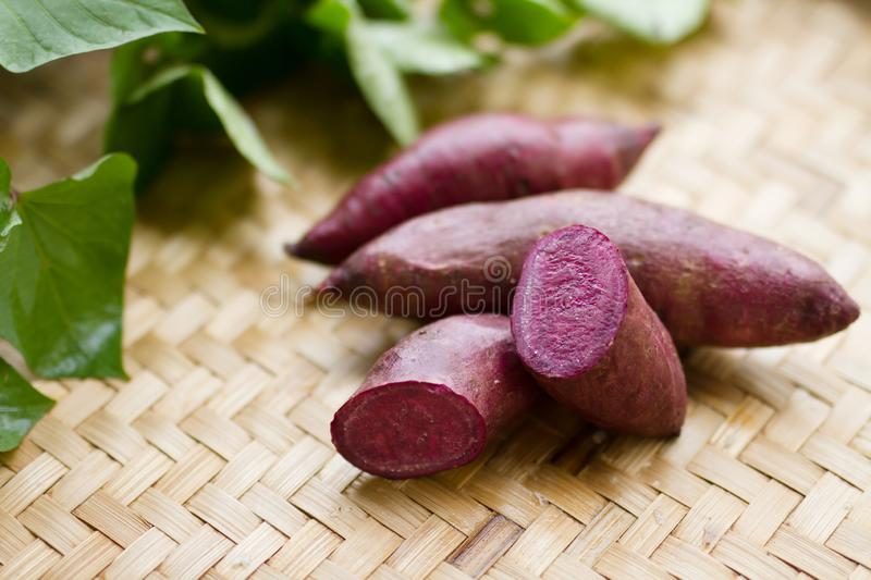 Purple sweet potato and leaf on weave wooden basket royalty free stock photos