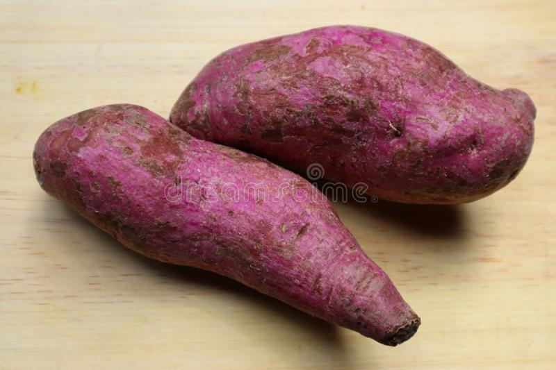Purple sweet potato. Isolated with wooden background royalty free stock images