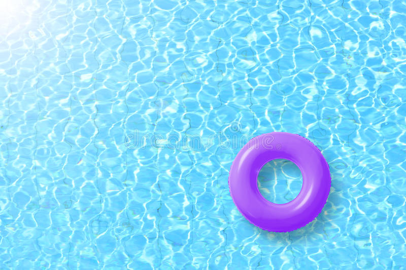 Purple swimming pool ring float in blue water and sun bright. Concept color summer royalty free stock photos