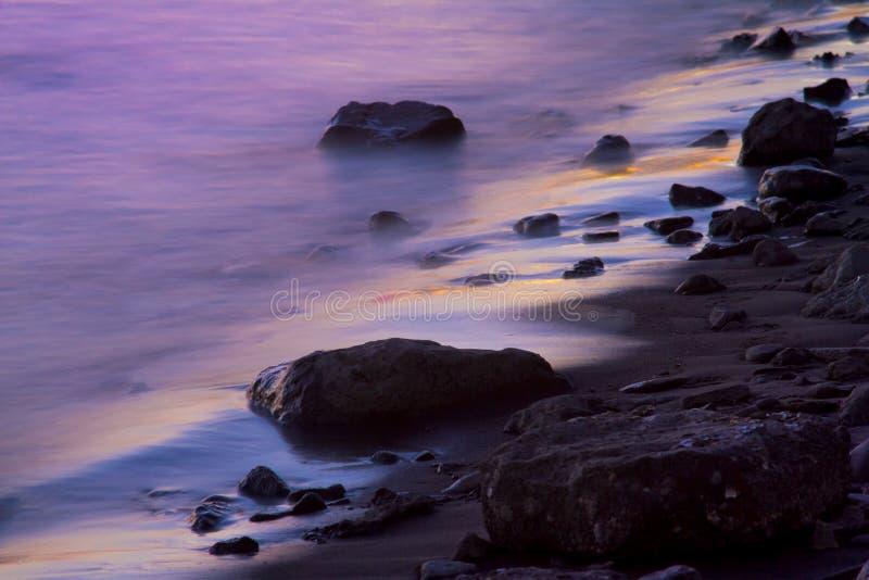 Purple tide. Gentle wave hitting beach and rocks in purple light stock photos
