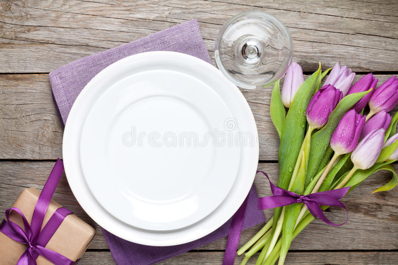 Purple tulip bouquet and plate on wooden table royalty free stock photography