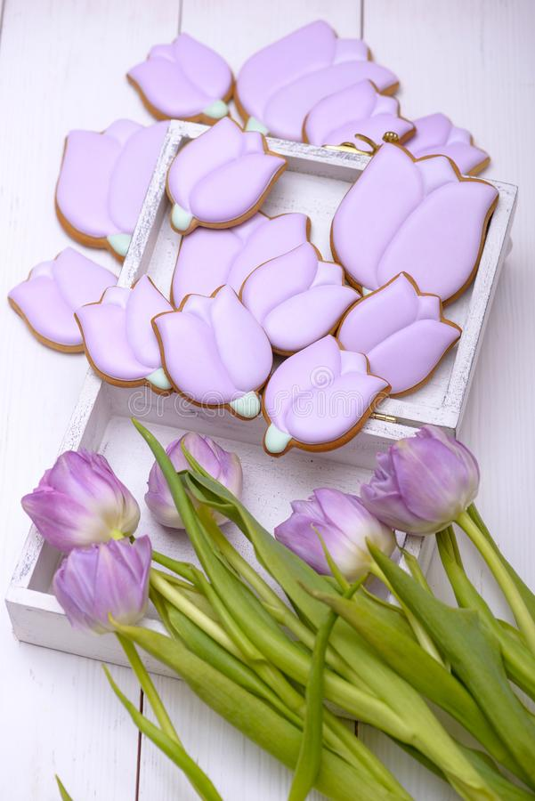Purple tulips and gingerbread cookies in the shape of flower stock photos