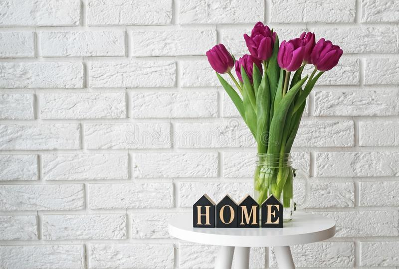 Purple tulips in a glass jar and wooden letters arranged into a word Home royalty free stock photos