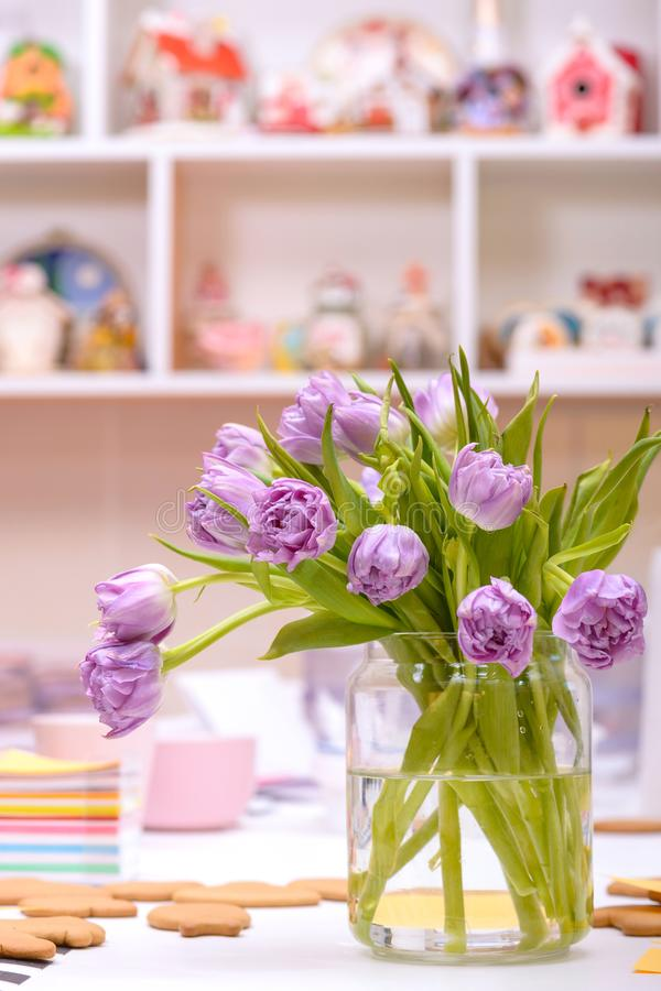 Purple tulips in vase on table stock images
