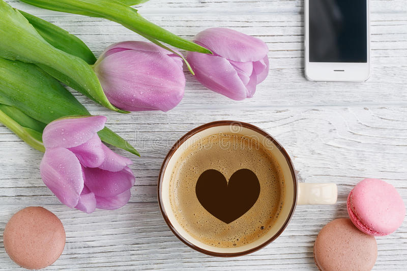 Purple tulips on wooden table. Purple tulips, coffee, smartphone and sweet pastel french macaroons on wooden table stock photo