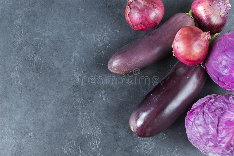 Purple vegetables, eggplant, cabbage, red onion on black. Background,  background stock images