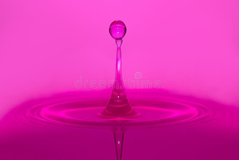 Purple water drop splash. High speed purple water drop splashing stock photos
