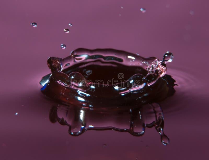 Purple water drop splash. In a waterbath royalty free stock photo