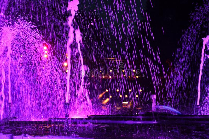Purple water-fontain at night. Sparkles of water illuminated by strong purple lights stock photos
