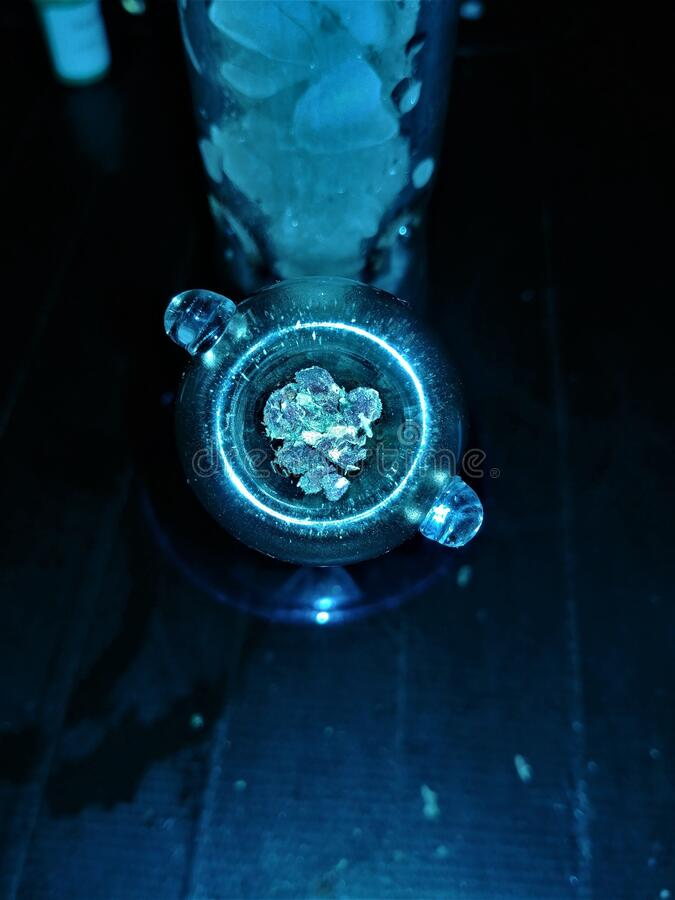 Purple Weed Packed inside Glass Bowl in Bong with Ice. In the chamber, black duct tape background stock photography