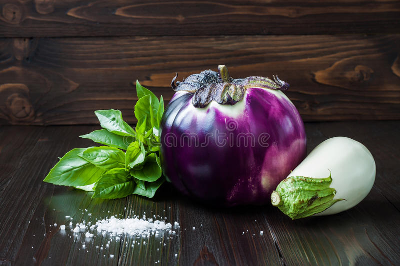Purple and white eggplant (aubergine) with basil on dark wooden table. Fresh raw farm vegetables - harvest from the gard. En in rustic kitchen. Rural still life stock photos