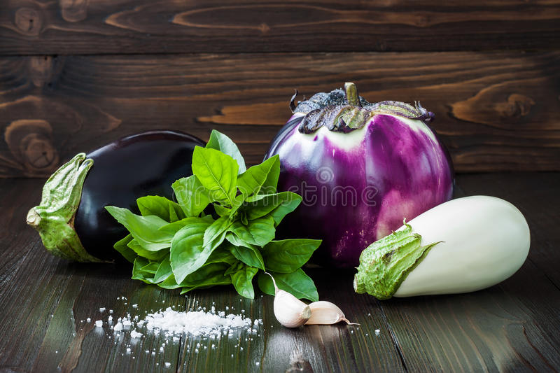 Purple and white eggplant (aubergine) with basil and garlic on dark wooden table. Fresh raw farm vegetables - harvest fr stock image