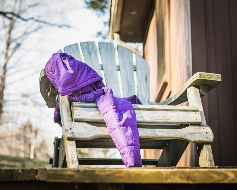 Purple Winter Coat Draped over an Aqua Adirondack Chair. Purple, down, winter coat draped over an aqua Adirondack chair sitting on a porch outside a cabin royalty free stock images