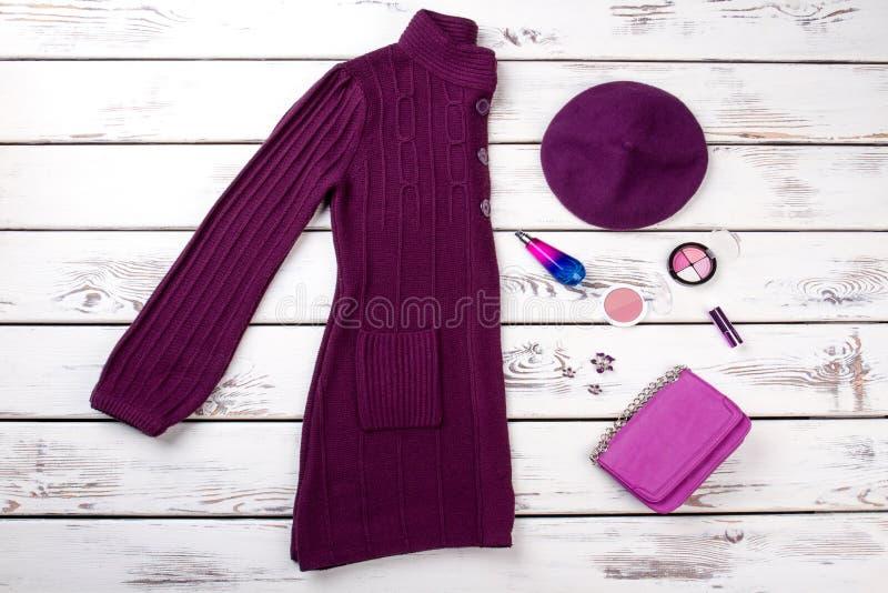 Purple women winter clothes set. Make up accessories, pink purse, burgundy hat stock image