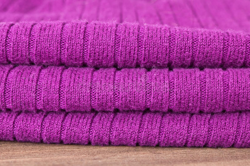 Purple wool. Folded purple wool fabric on a wooden surface stock images