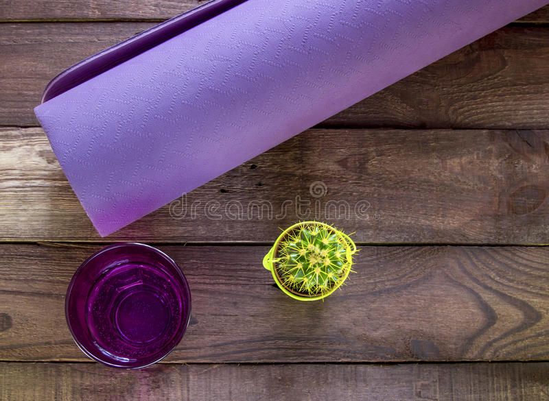 Purple yoga mat with glass of water and cactus on a dark wooden. Floor stock image