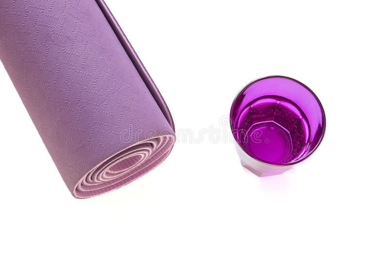 Purple yoga mat with glass of water isolated in a white background.  royalty free stock photos