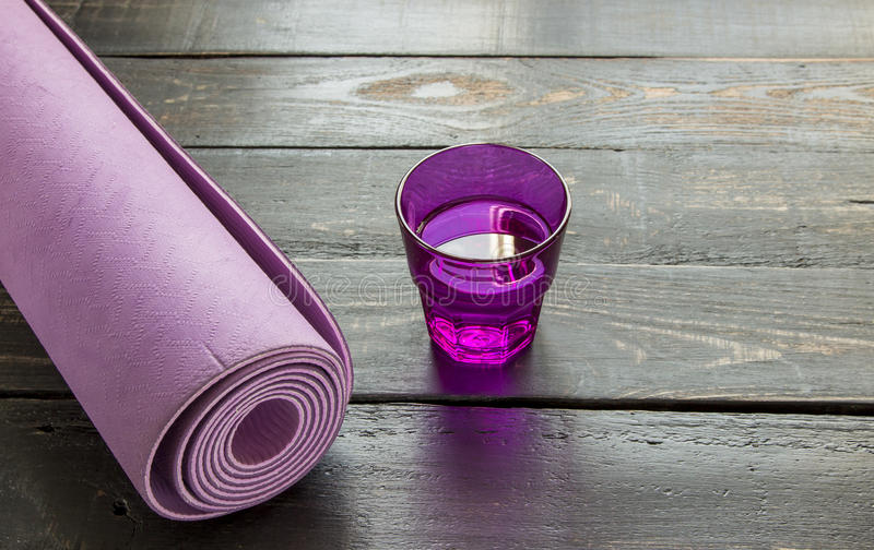 Purple yoga mat in a roll with glass of water on a dark wood.  stock photography