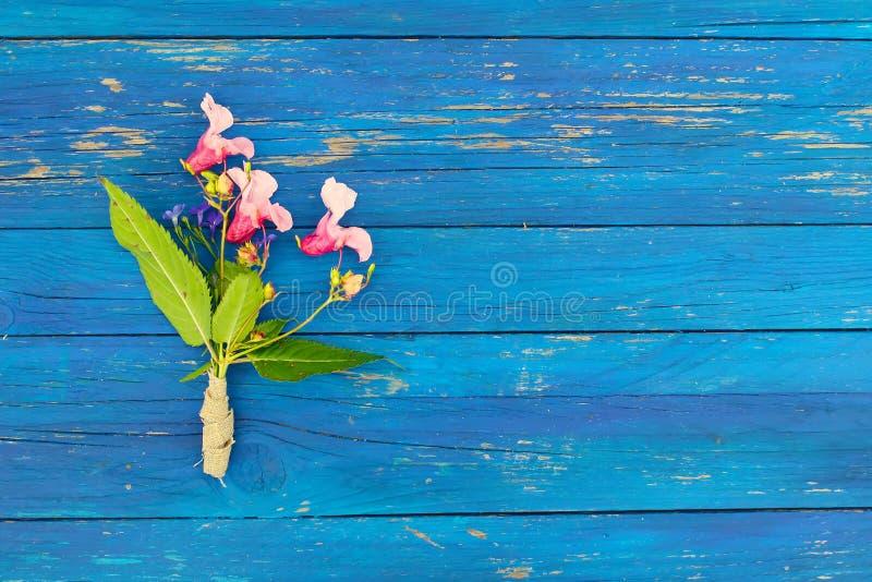Purpleheartbeschaffenheit mit kleinem Blumenstrauß des indischen Balsams blüht Impatiens-glandulifera Anlage Natürliches hölzerne lizenzfreie stockfotos