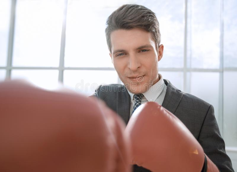Purposeful young businessman in Boxing gloves. Concept of competitiveness stock photo