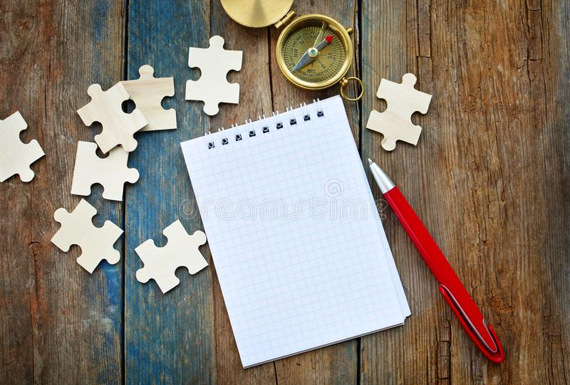 Purposes, goals and strategy building concept. Empty paper notepad, compass navigation, puzzles and pen. On a rustic table royalty free stock photo